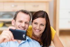 Lyckliga par som ser fotona på kameran Fotografering för Bildbyråer