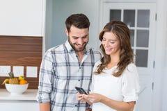 Lyckliga par som ser i mobiltelefon Arkivfoto