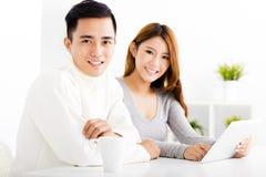Lyckliga par som ser minnestavlan i vardagsrum Royaltyfria Foton