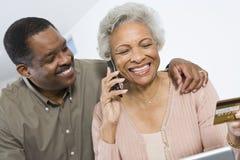Lyckliga par som shoppar direktanslutet genom att använda kreditkorten Arkivfoto