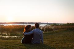 Lyckliga par som sitter på gräset som framme håller ögonen på solnedgången av en sjö royaltyfri fotografi