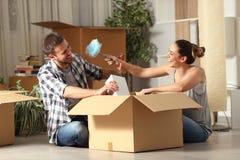 Lyckliga par som skojar det unboxing r?rande hemmet f?r tillh?righeter arkivbilder