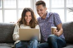 Lyckliga par som skrattar att se på bärbar datorskärmsammanträde på soffan royaltyfri foto