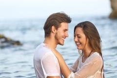 Lyckliga par som skrattar badning på stranden royaltyfria foton