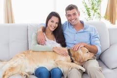 Lyckliga par som slår hunden, medan sitta på soffan Fotografering för Bildbyråer