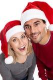 Lyckliga par som slitage santa hattar Arkivfoto