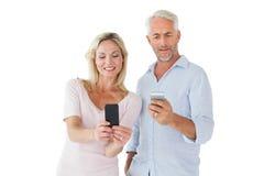 Lyckliga par som smsar på deras smartphones Fotografering för Bildbyråer