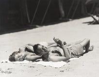 Lyckliga par som solbadar på stranden Royaltyfri Bild
