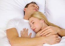 Lyckliga par som sover i säng Arkivfoto