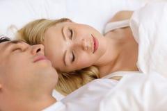 Lyckliga par som sover i säng Arkivbilder