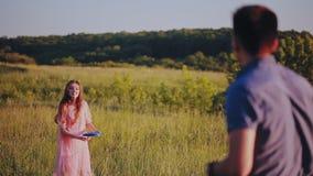 Lyckliga par som spelar frisbeen ut ur stad på en solig sommardag arkivfilmer