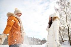 Lyckliga par som spelar med insnöad vinter royaltyfria bilder