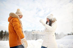 Lyckliga par som spelar med insnöad vinter royaltyfria foton