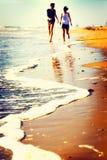 Lyckliga par som spelar på kusten på solnedgången royaltyfri bild