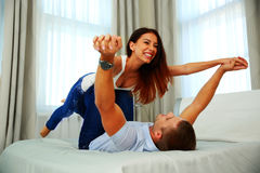 Lyckliga par som spelar på sängen Royaltyfria Foton