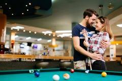 Lyckliga par som spelar snooker royaltyfri bild