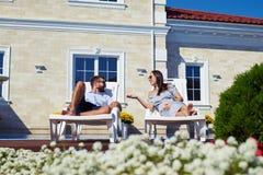 Lyckliga par som talar, medan koppla av på vardagsrumstolar framme av Royaltyfri Fotografi
