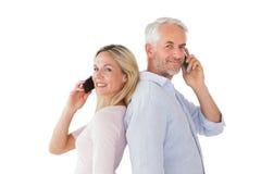 Lyckliga par som talar på deras smartphones Royaltyfri Bild