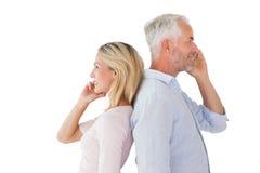Lyckliga par som talar på deras smartphones Fotografering för Bildbyråer