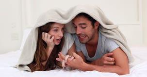 Lyckliga par som talar på sängen lager videofilmer