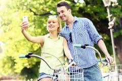 Lyckliga par som tar bilder av dem på en cykel Fotografering för Bildbyråer