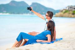 Lyckliga par som tar ett foto på den vita stranden på bröllopsresaferie fotografering för bildbyråer