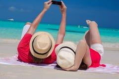 Lyckliga par som tar ett foto själva på den tropiska stranden Fotografering för Bildbyråer