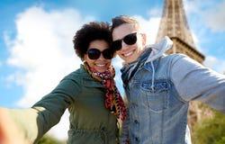 Lyckliga par som tar selfie över Eiffeltorn Royaltyfri Bild
