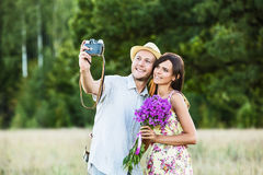 Lyckliga par som tar selfie fotografering för bildbyråer