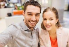 Lyckliga par som tar selfie i galleria eller kontor Royaltyfri Foto