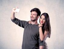 Lyckliga par som tar selfie med den klara väggen Arkivbilder