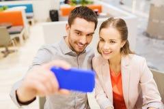 Lyckliga par som tar selfie med smartphonen i kafé Royaltyfri Fotografi