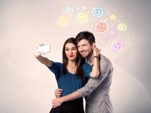 Lyckliga par som tar selfie med smiley Arkivfoton
