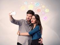 Lyckliga par som tar selfie med smiley Royaltyfri Bild