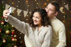 Lyckliga par som tar selfie och har gyckel i julgarnering Mörk träinre med ljus Den romantiska aftonen och förälskelse lurar Arkivbilder