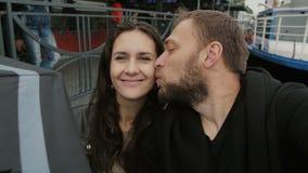 Lyckliga par som tar selfie, punkt-av-sikt skott man och förälskat le för kvinna på kameran som kysser på en kind, långsam mo arkivfilmer
