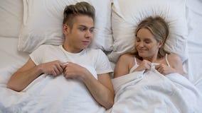 Lyckliga par som till varandra ler att ligga i säng, första intimitet, förälskelseerfarenhet arkivfoto