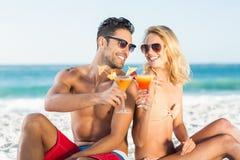 Lyckliga par som tillbaka sitter för att dra tillbaka att dricka coctailen Royaltyfri Foto