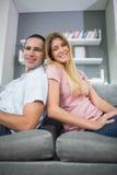 Lyckliga par som tillbaka sitter för att dra tillbaka på soffan tillsammans Royaltyfri Bild