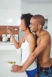 Lyckliga par som tillsammans äter frukt Royaltyfria Bilder