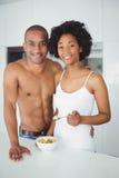 Lyckliga par som tillsammans äter frukt i köket Arkivbild