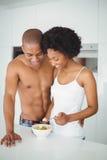 Lyckliga par som tillsammans äter frukt i köket Royaltyfria Foton