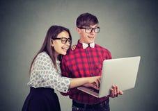 Lyckliga par som tillsammans delar bärbara datorn fotografering för bildbyråer