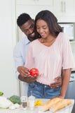 Lyckliga par som tillsammans förbereder mat arkivfoton