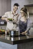 Lyckliga par som tillsammans förbinder, medan laga mat ett mål i köket som dricker vin Arkivbild