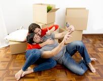 Lyckliga par som tillsammans flyttar sig i ett nytt hus som tar selfievideoen och pic Royaltyfri Fotografi