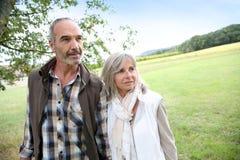 Lyckliga par som tillsammans går i fält Royaltyfria Foton