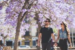 Lyckliga par som tillsammans går nära härliga träd Arkivfoto