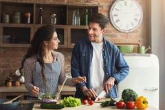 Lyckliga par som tillsammans lagar mat den sunda matställen royaltyfri foto