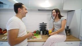 Lyckliga par som tillsammans lagar mat i köket långsam rörelse arkivfilmer